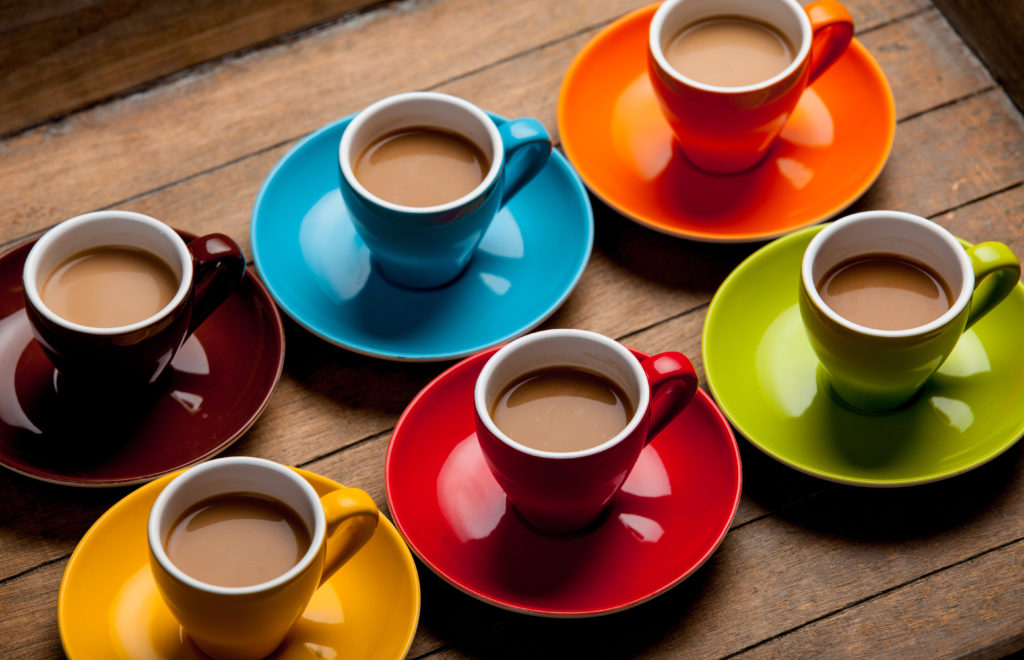 Six Colored Coffee cups on like colored plates filled with coffee and cream