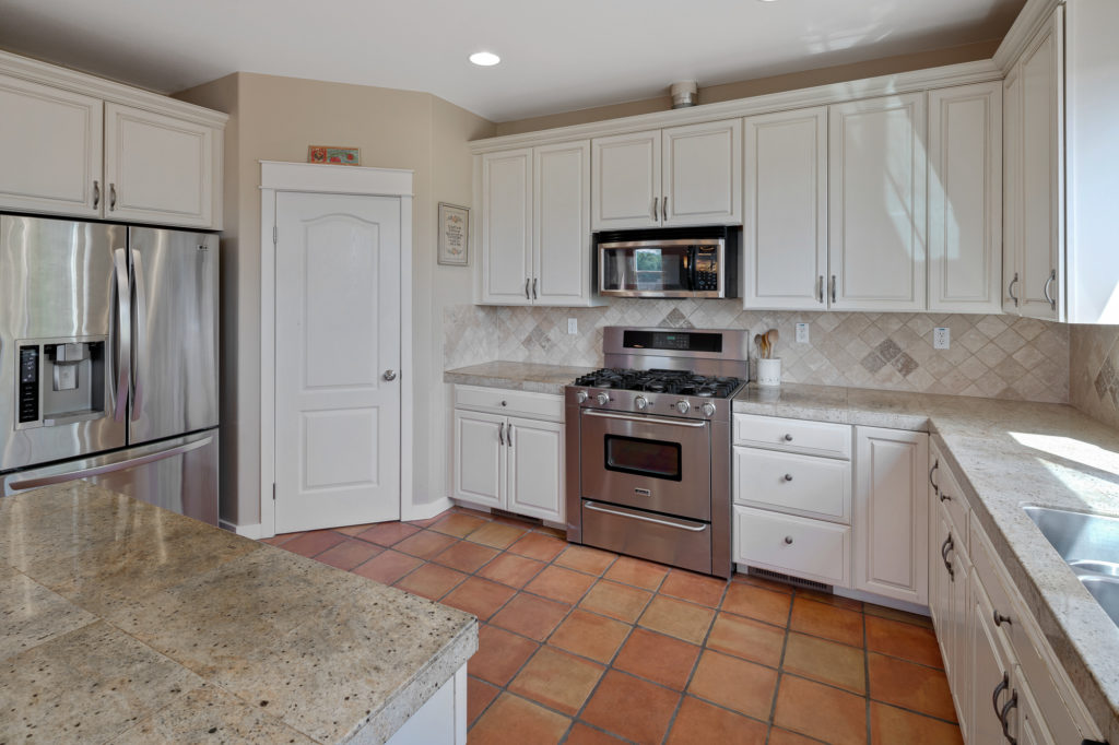 Beautiful white tone kitchen with stainless steel appliances, grey tone granite counters and ceramic tile back splash at 574 Hillside Dr Cloverdale CA Open House May 5 2019 from 2 p.m. to 4 p.m.