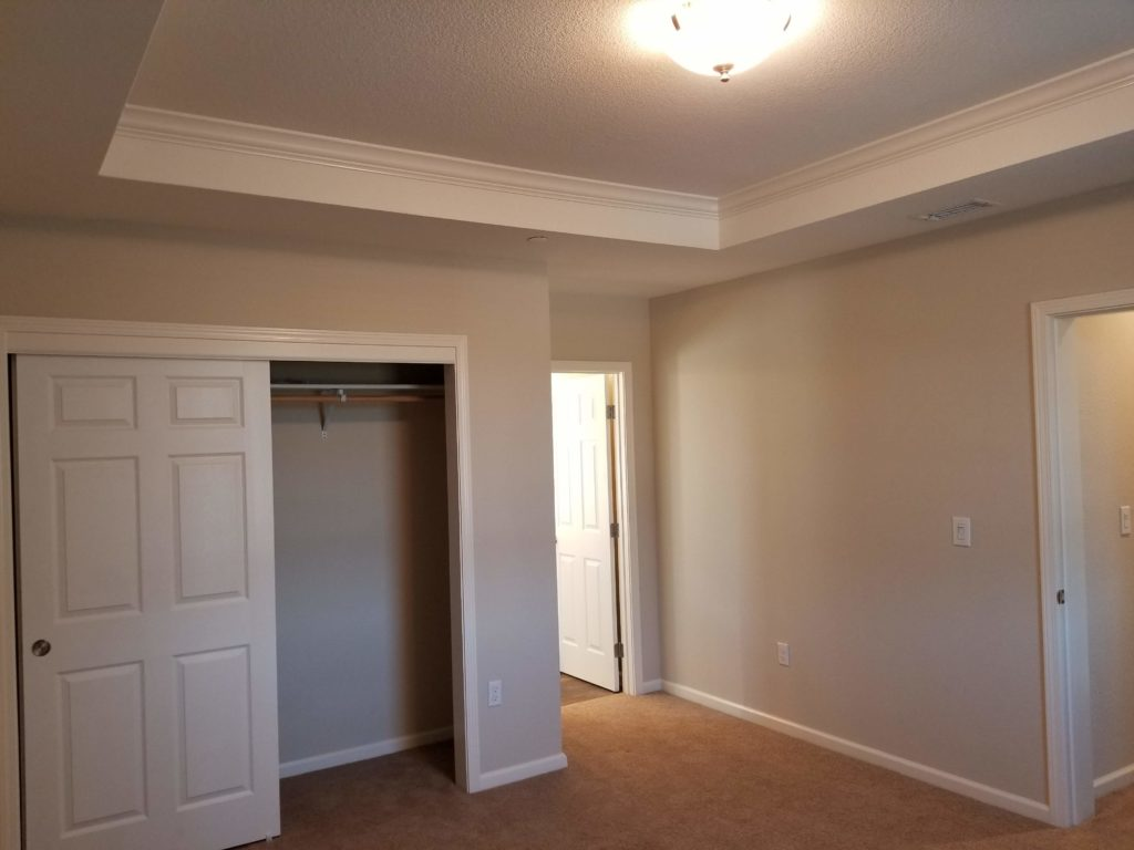 2057 Medano Dr Master bedroom with medium brown short shag carpet and a stepped ceiling