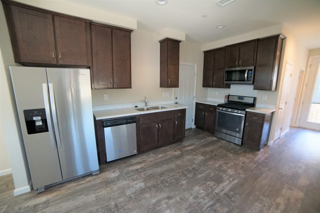 Open kitchen with dark brown cabinets and stainless steel appliances and a medium mixed brown vinyl plank floor