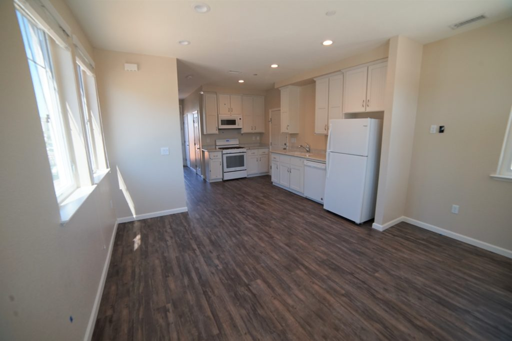 Living room to kitchen combo with dark vinyl plank flooring light beige walls white appliances and cabinets and light stone counters
