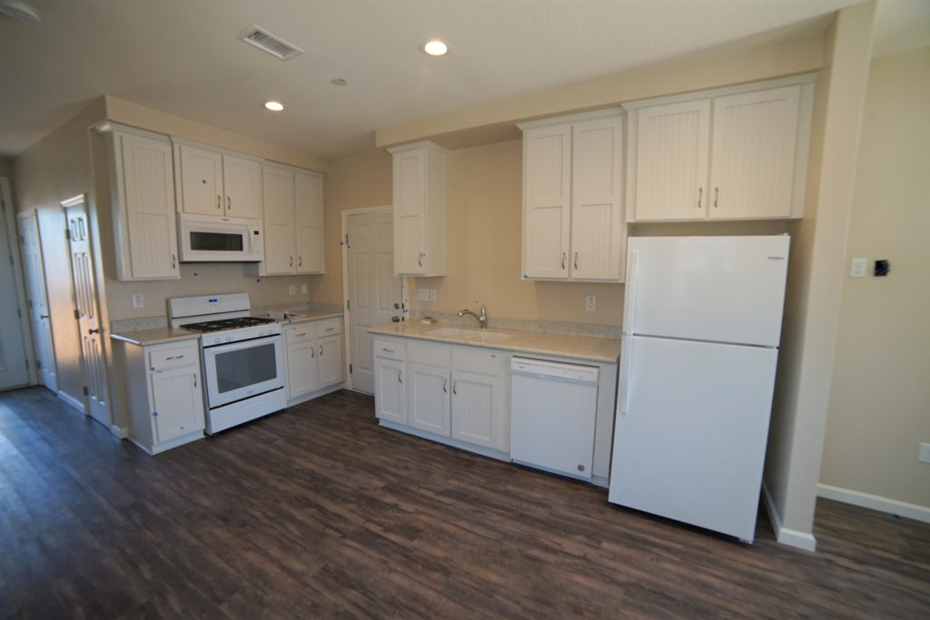 2059 Medano Dr Santa Rosa CA 95407 has a popular color scheme with white cabinets and appliances, light stone counters and dark vinyl plank flooring on the lower level