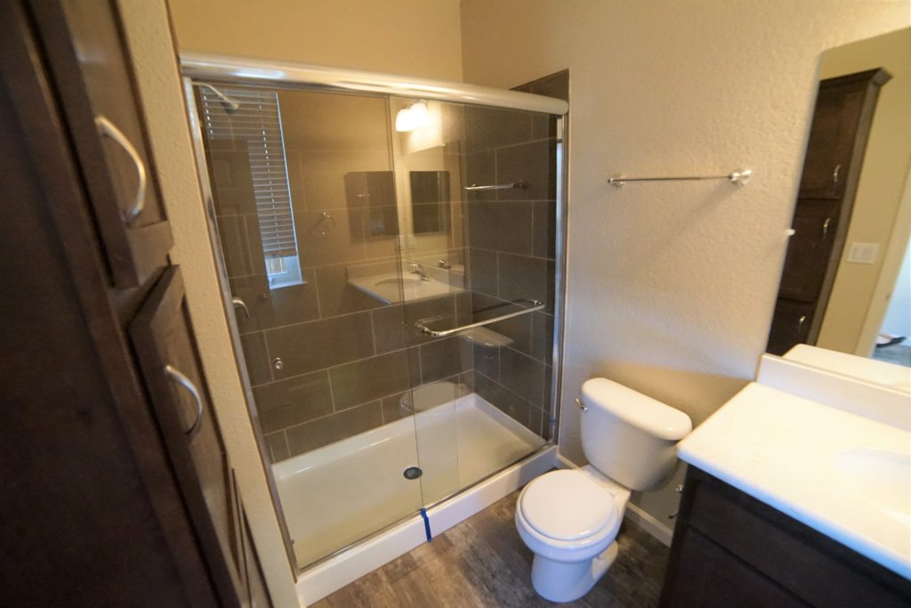 Full Bathroom Downstairs with a vanity and walk in shower that have glass doors same color scheme as kitchen