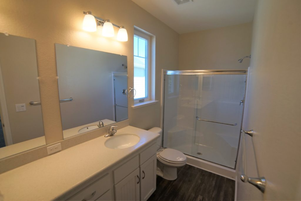 The master bathroom at 2059 Medano Dr has the same color pallet as the other two bathrooms and the kitchen which is white cabinet and light stone counters and like tile