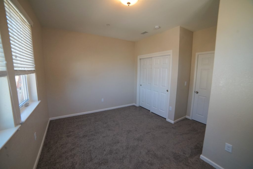 The third bedroom of 2059 Medano Dr also has medium brown short shag carpet and faces homes that have already been built
