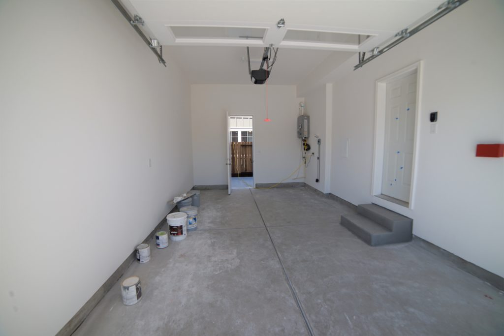 Looking in at the finished garage at 2057 Medano Dr with concrete floor and two steps that lead into the houses kitchen area