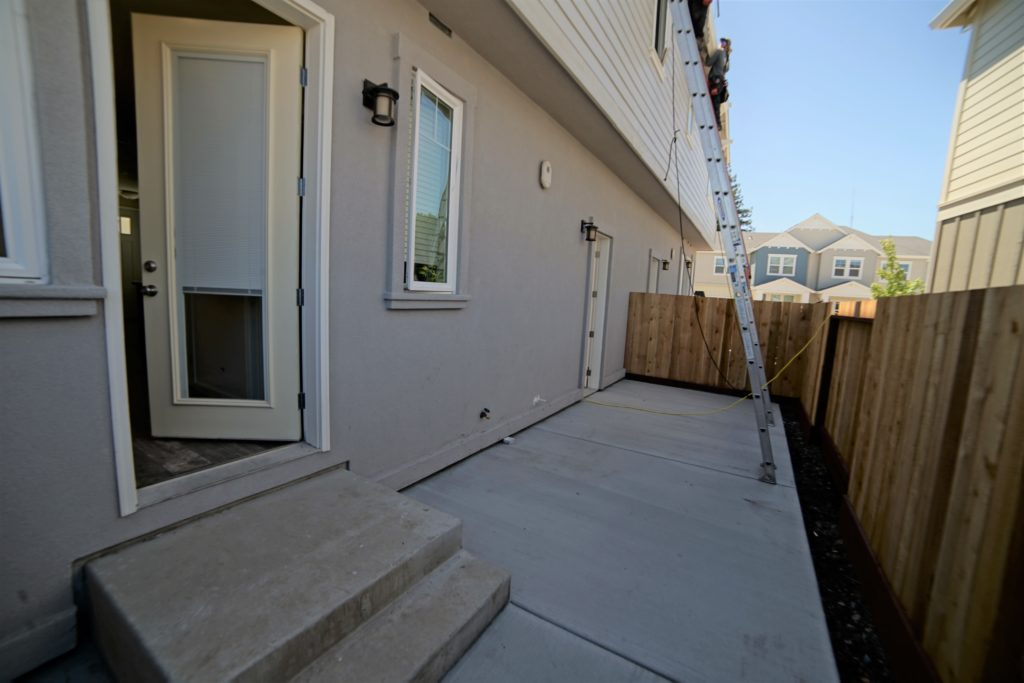 Personal concrete patio backyard with perimeter fencing. Access from garage without steps or inside house with two steps.
